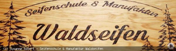 ovales Logo der Firma Wladseifen Seifenschule & Manufaktur Nordschwarzwald mit Tannen rechts und links umrahmt