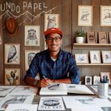 Ein junger Mann mit roter Cap sitzt mit Stift an einem Tisch, auf dem sehr viele Bleistiftzeichnungen sowie Stifte liegen. Dahinter an der Holzwand sind weitere Zeichnungen zu sehen.