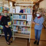 Zwei Menschen mit Maske vor einem Bücherregal in der Stadtbücherei