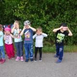 sechs Kinder die sich auf einem schmalen geteerten Weg die Hände vor die Augen halten