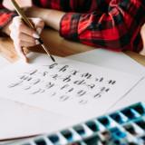 ein Mensch sitzt am Tisch und malt mit einem Pinsel geschwungene Buchstaben auf ein Blatt
