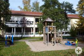 Großes Haus mit Spielplatz im Vordergrund