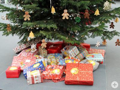 Bunt verpackte Weihnachtsgeschenke unter einem geschmückten Tannenbaum
