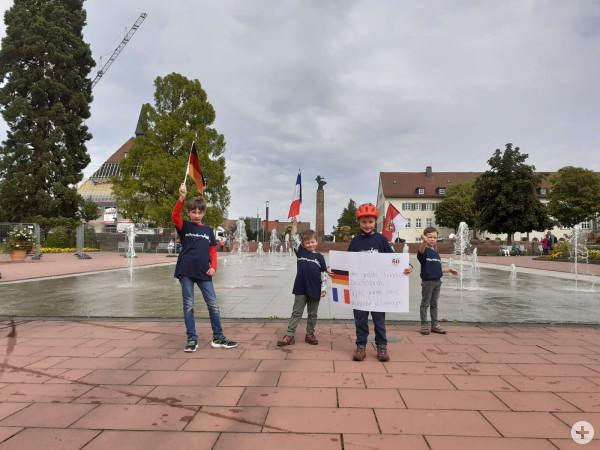 Kinder zeigen ein Plakat vor den Fontänen auf dem Marktplatz zur Städtepartnerschaft