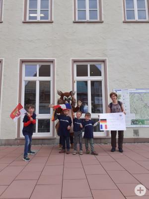 Kinder zeigen ein Plakat vor dem technischen Rathaus zur Städtepartnerschaft