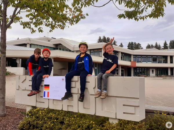 Kinder zeigen ein Plakat vor der Keplerschule zur Städtepartnerschaft