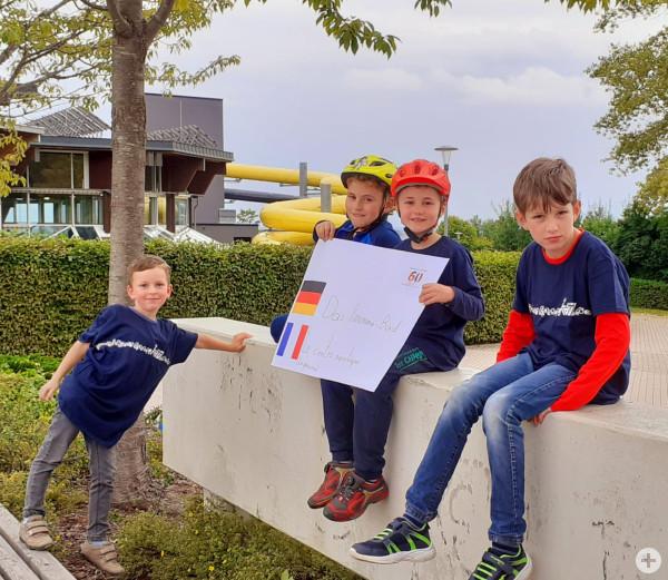 Kinder zeigen ein Plakat vor dem Panorama-Bad zur Städtepartnerschaft