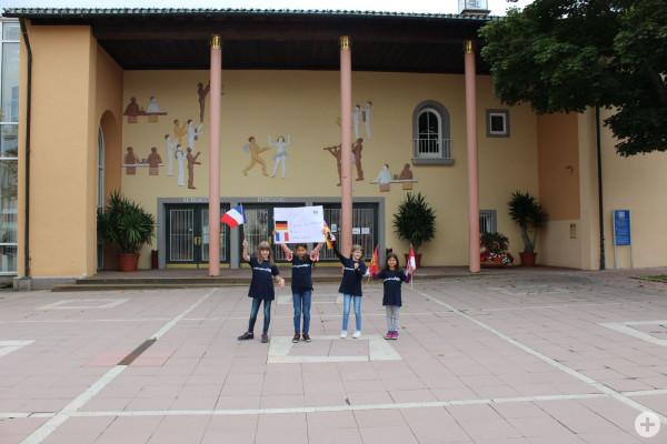 Kinder zeigen ein Plakat vor dem Kurhaus zur Städtepartnerschaft