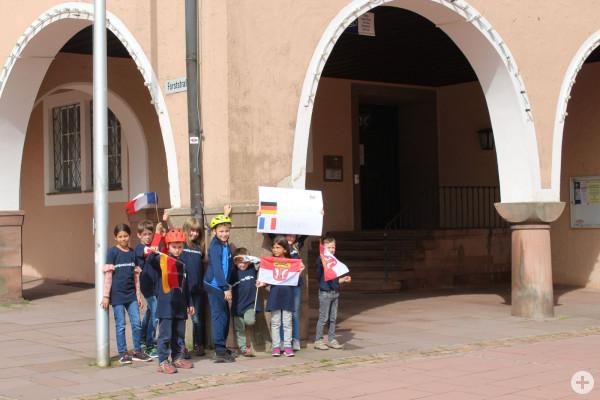 Kinder zeigen ein Plakat vor dem Rathaus zur Städtepartnerschaft