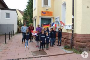 Kinder zeigen ein Plakat vor dem Kinder- und Jugendzentrum zur Städtepartnerschaft