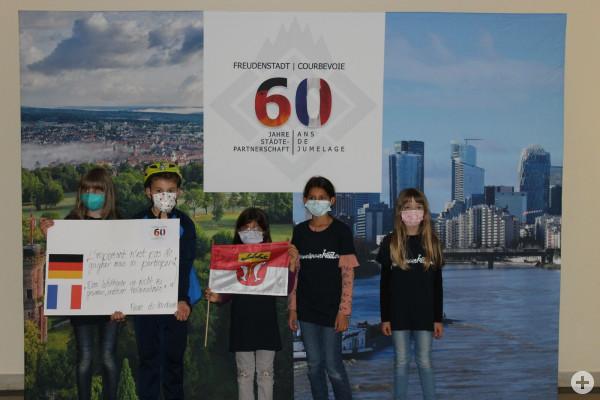 Kinder zeigen ein Plakat im Rathaus zur Städtepartnerschaft