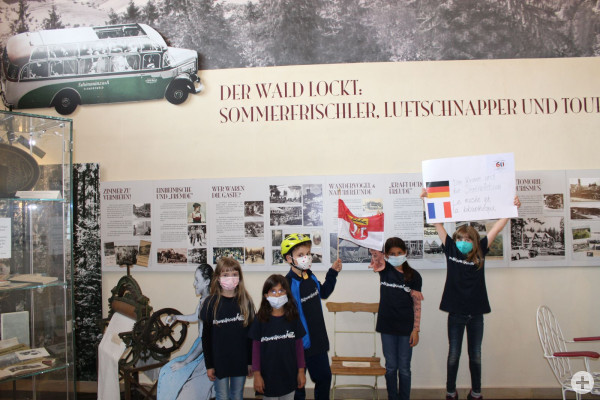Kinder zeigen ein Plakat im Museum im Stadthaus zur Städtepartnerschaft