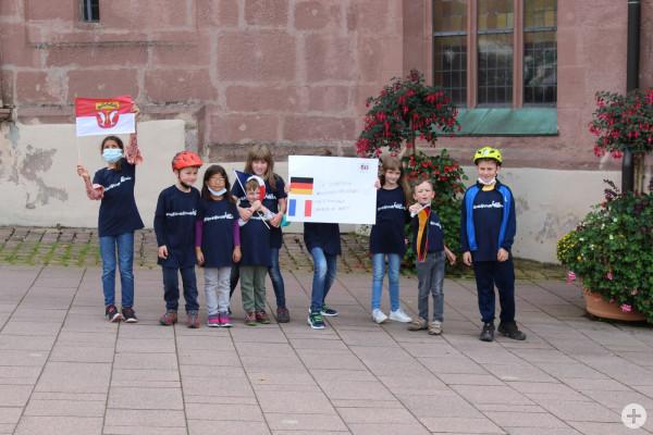 Kinder zeigen ein Plakat vor der Stadtkirche zur Städtepartnerschaft