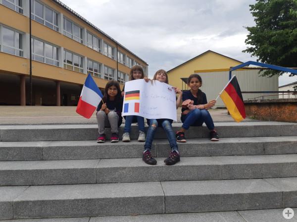 Kinder zeigen ein Plakat vor der Realschule zur Städtepartnerschaft