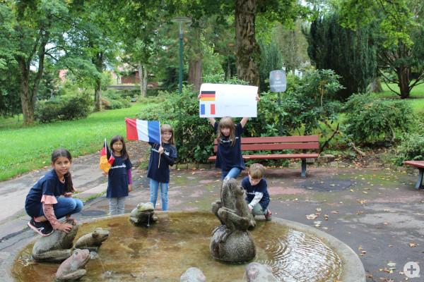 Kinder zeigen ein Plakat im Park Courbevoie zur Städtepartnerschaft