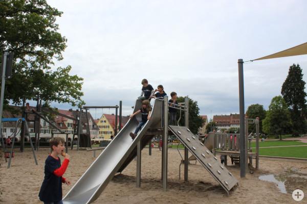 Kinder zeigen ein Plakat auf dem Spielplatz am Marktplatz zur Städtepartnerschaft