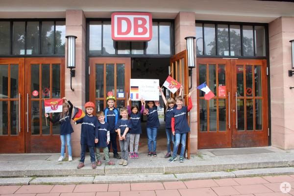Kinder zeigen ein Plakat vor dem Stadtbahnhof zur Städtepartnerschaft
