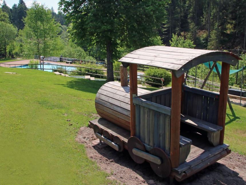 Die Spiellok mit Blick auf das Schwimmbecken im Waldschwimmbad Kniebis